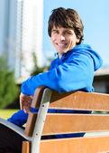 Jeune homme assis sur un banc — Photo
