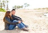 Junges paar sitzt am strand — Stockfoto