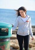 Mulher jogando papel na lata de lixo — Foto Stock