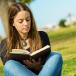 Woman Reading Book In Park - Stock Photo