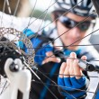 Male Cyclist Inflating Tire Of Bicycle - Foto Stock
