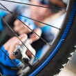 Stock Photo: Male Cyclist Inflating Tire Of Bicycle