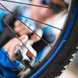 Male Cyclist Inflating Tire Of Bicycle - Stock Photo