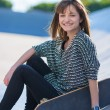 Happy Woman Sitting with Skateboard — Stock Photo