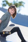 šťastná žena, sedící s skateboard — Stock fotografie