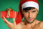 Sexy Santa Claus with present — Stock Photo