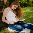 Stock Photo: Teen Girl Reading in yard