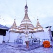 White pagoda with monk - Stock Photo