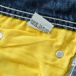 Laundry advice care symbols on blue jeans — Stock Photo