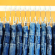 Stock Photo: Row of hanged blue jeans