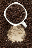 Cup full of coffee beans on the old map — Stock Photo