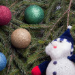 Royalty-Free Stock Photo: Colorful balls and snowman lying on spruce branches.