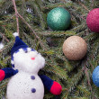colorful balls and snowman lying on spruce branches. — Stock Photo