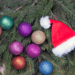 Santa Claus hat and colorful balls are on the fir branches — Stock Photo #22308165