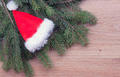 Santa's hat hanging on fir branches — Stock Photo