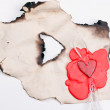 Mark in the shape of a heart made of red wax on a piece of burnt — Stock Photo