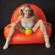 Blonde on the orange chair. — Stock Photo