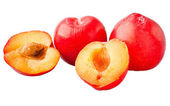 Two red plums and plum halves. — Stock Photo