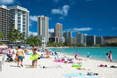 Tourist sunbathing and surfing on the Waikiki beach in Hawaii. — Stok fotoğraf