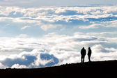 Tourist silhouette watching sunset on the top of  Haleakala volc — Stock Photo