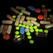 Colored pills on black background — Stock Photo #32006907