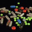 Colored pills on black background — Stock Photo #32007043