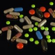 Colored pills on black background — Stock Photo