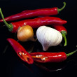 Red hot pepper with onions and garlic on black background — Stock Photo