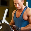 Strong man preparing his training machine in fitness  — Stock Photo