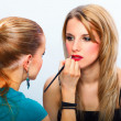Make-up artist applying lipstick on model's lips — Stock Photo