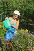 The girl is watering the flowers — Stock Photo