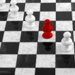 RED PAWN STANDING OUT IN A GROUP OF WHITE PAWNS — Stock Photo