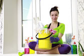 Woman with cleaning equipment sitting by a window — Stock Photo