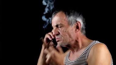 Senior man talking on mobile phone and smoking cigar on black background — Stock Video