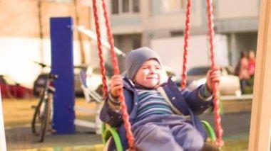 Boy riding on a swing — Стоковое видео