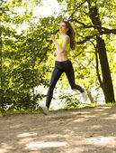 Sports girl runs in park effect films — Stock Photo