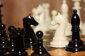 Chessmen on a chessboard on a dim background — Stock Photo