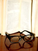 Spectacles on background of the revealled book — Stock Photo