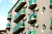 Building with green balconies — Stock Photo