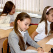Stock Photo: Girls at a lesson at school sit at a school desk