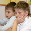 Two boys sit at school at a school desk — Stockfoto