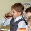 The boy in school cafeteria drinks drink — Stock Photo