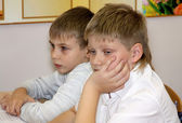 Two boys sit at school at a school desk — Stock Photo
