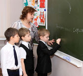 The teacher with pupils costs at a blackboard in a class — Stock Photo