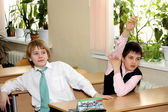 Two boys at school at a lesson sit at a school desk — Stock Photo