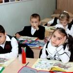 Children at a lesson sit at school desks — Stock Photo