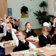 Children at school at a lesson lift hands — Stock Photo #12850340