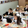 Children at school at a lesson write in writing-books — Stock Photo #12850344