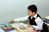 El niño con un libro de escritura se sienta en un pupitre en una lección — Foto de Stock