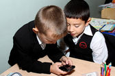 Two boys dial number on the mobile phone — Stock Photo